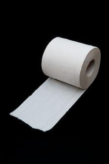 Einzelne rolle abgerolltes weißes toilettenpapier auf schwarzem hintergrund isoliert