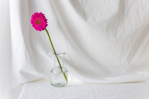 Einzelne rosa gerberablume im vase auf weißem schreibtisch