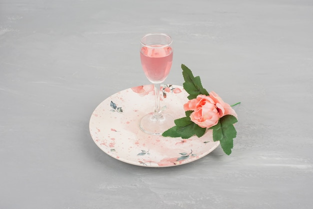 Einzelne rosa rose und ein glas roséwein auf rosa teller