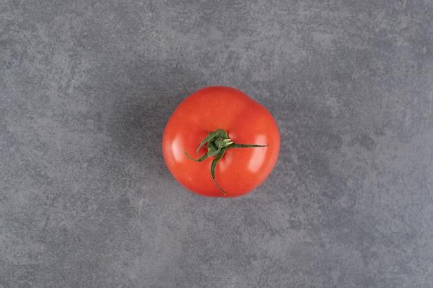 Einzelne rote tomate auf marmorhintergrund. foto in hoher qualität