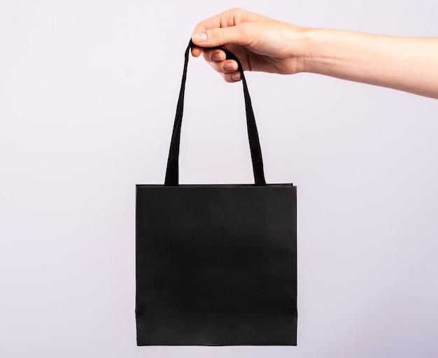 Einzelne schwarze tasche der nahaufnahme gehalten