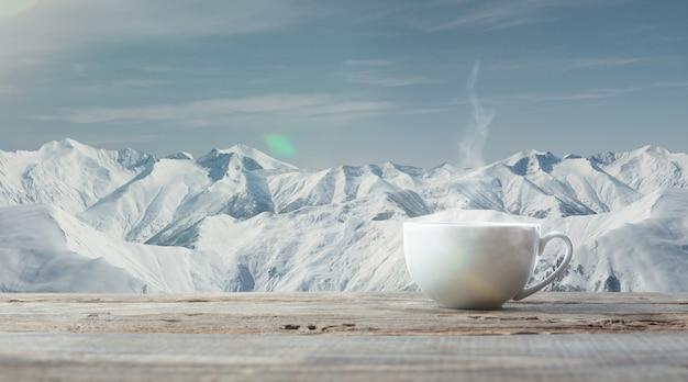 Einzelne tee- oder kaffeetasse und berglandschaft im hintergrund. tasse heißes getränk mit schneebedecktem blick und bewölktem himmel davor. warm an wintertagen, feiertagen, reisen, neujahr und weihnachten.