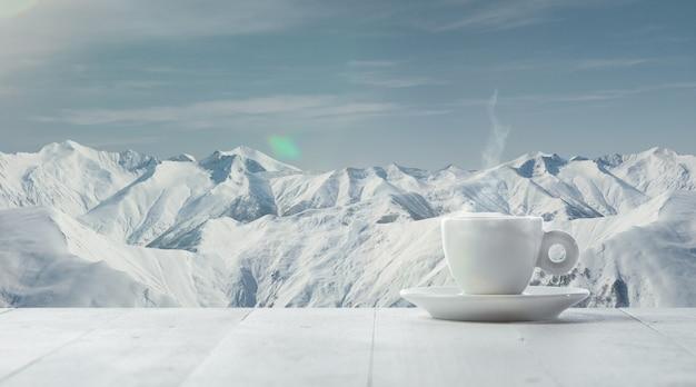 Einzelne tee- oder kaffeetasse und berglandschaft im hintergrund