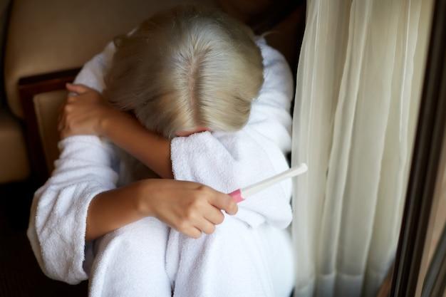 Einzelne traurige frau, die einen schwangerschaftstest zu hause halten sitzt auf einer couch im wohnzimmer sich beschwert