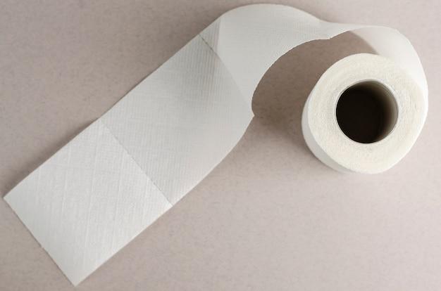 Einzelne weiße toilettenpapierrolle auf grau