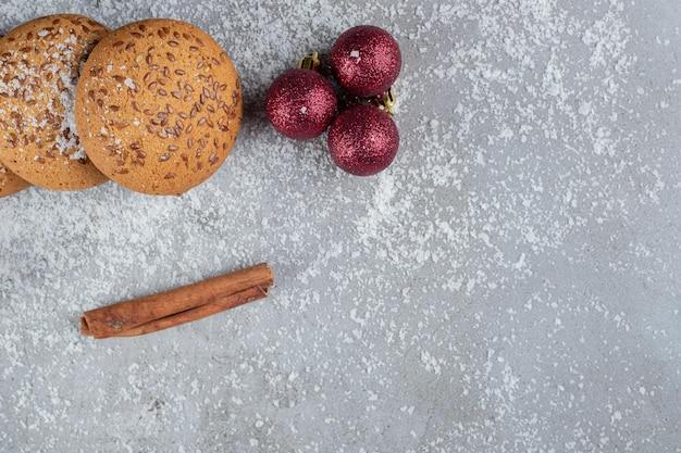 Einzelne zimtstange, kekse, dekorative kugeln und ein zweig auf marmoroberfläche