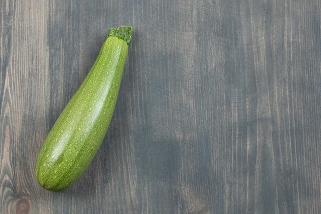 Einzelne zucchini oder zucchini isoliert auf einem holztisch