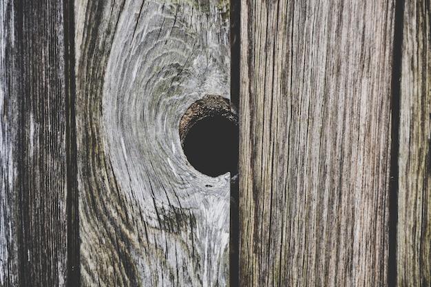 Einzelner dunkler holzknoten in der strukturierten holzplanke aus altem holz