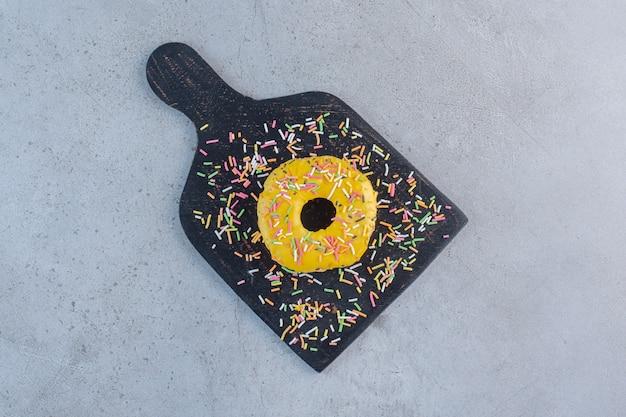 Einzelner gelber donut verziert mit streuseln auf schneidebrett.