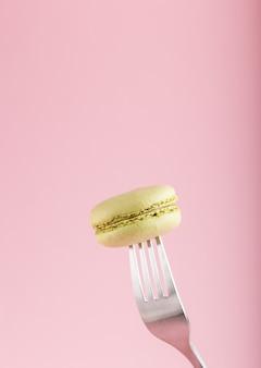 Einzelner grüner macaron- oder makronenkuchen auf einer gabel auf pastellrosa hintergrund. seitenansicht.