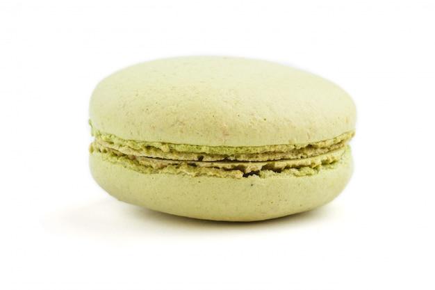 Einzelner grüner macaron oder makronenkuchen lokalisiert auf weißem hintergrund, seitenansicht.