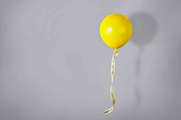 Einzelner hellgelber ballon, der gegen graue wand fliegt. farbtrends im jahr 2021. positives konzept. speicherplatz kopieren