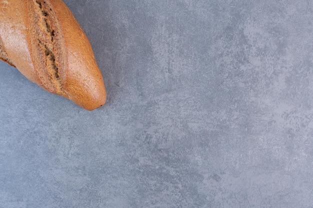 Einzelner laib taktstockbrot auf marmorhintergrund. foto in hoher qualität