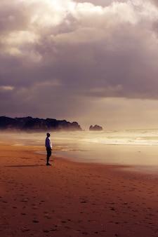 Einzelner mann an einem strand mit blick auf die ewigkeit des ozeans an einem bewölkten und sandigen strand.