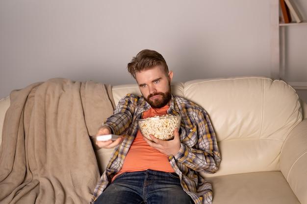 Einzelner mann auf der couch, die fernsieht