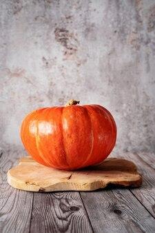Einzelner orange kürbis auf rustikalem holztablett. herbstkonzept, ernte, halloween, erntedankfest