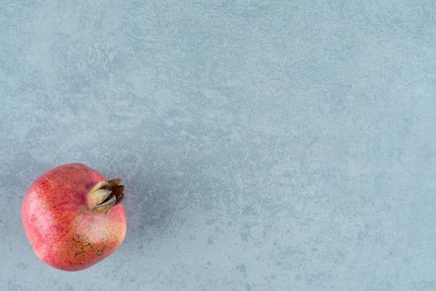 Einzelner roter granatapfel auf marmor.
