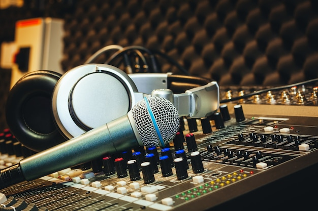 Einzelnes mikrofon mit kopfhörern auf tonmischerbrett im hauptaufnahmestudio.
