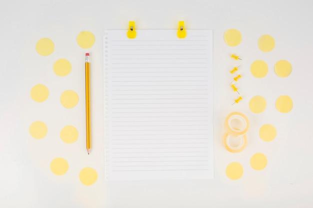 Einzelnes papier und bleistift umgeben mit elementen auf weißem hintergrund