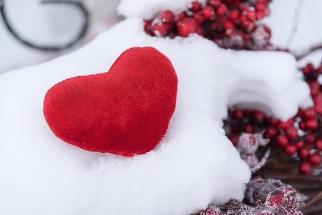 Einzelnes rotes herz auf schnee. valentinstag, liebeskonzept.