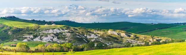 Einzigartige grüne landschaft in der toskana, italien. dramatischer sonnenuntergangshimmel, schotterstraße, die kultivierte hügelkette und getreidefelder überquert.