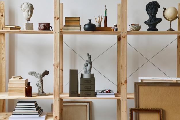 Einzigartiger künstlerarbeitsplatz mit stilvollem schreibtisch, holzstaffelei, bücherregal, kunstwerken, malzubehör, dekoration und eleganten persönlichen sachen. modernes arbeitszimmer für künstler. vorlage.