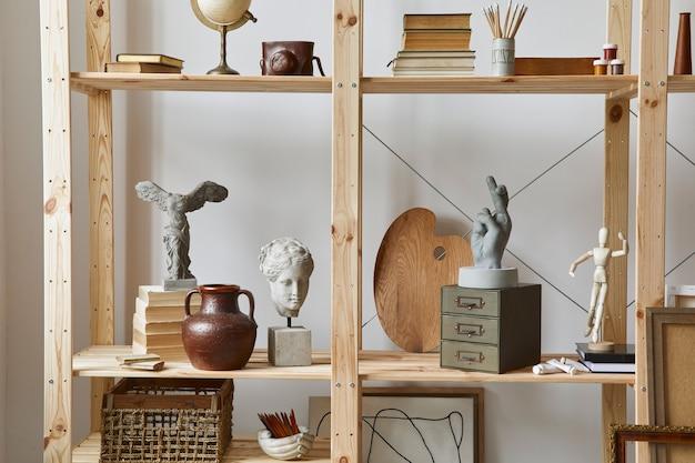 Einzigartiger künstlerarbeitsplatz mit stilvollem schreibtisch, holzstaffelei, bücherregal, kunstwerken, malzubehör, dekoration und eleganten persönlichen sachen. modernes arbeitszimmer für künstler.