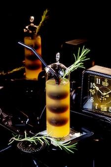 Einzigartiges glas eines zweifarbigen cocktails, garniert mit rosmarin