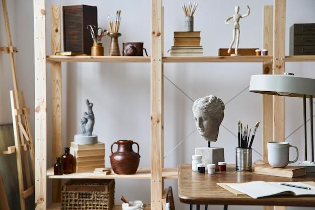 Einzigartiges interieur für künstlerarbeitsplätze mit stilvollem schreibtisch, hölzerner staffelei, bücherregal, kunstwerken, malzubehör, dekoration und eleganten persönlichen dingen. moderner arbeitsraum für künstler.