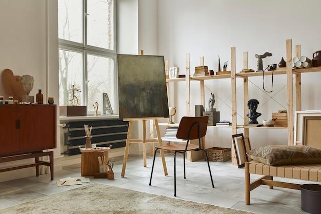 Einzigartiges interieur für künstlerarbeitsplätze mit stilvoller teakholzkommode, hölzerner staffelei, bücherregal, kunstwerken, malzubehör, dekoration und eleganten persönlichen dingen. moderner arbeitsraum für künstler.