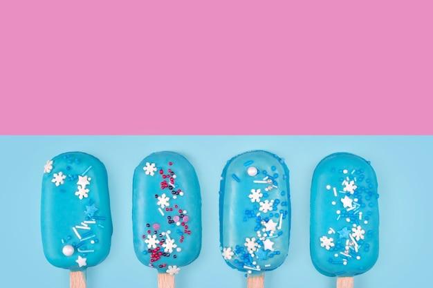 Eis am stiel der blauen minzeis auf blauem und rosa hintergrund. leckeres und erfrischendes eis am stiel. minimales sommerkonzept. flacher, freier copyspace für text