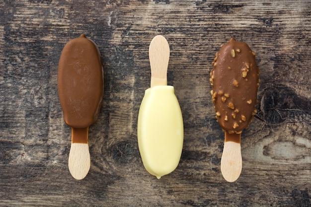 Eis am stiel der schwarzen und weißen schokoladeneis auf holztisch, draufsicht
