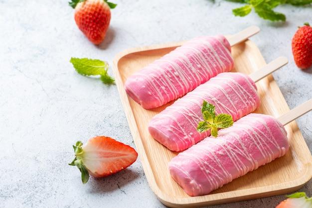 Eis erdbeer-milch-stick, mit milch bedeckt.