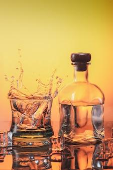 Eis fällt auf ein glas whisky und macht spritzer und eine flasche likör auf orangenbasis mit eis