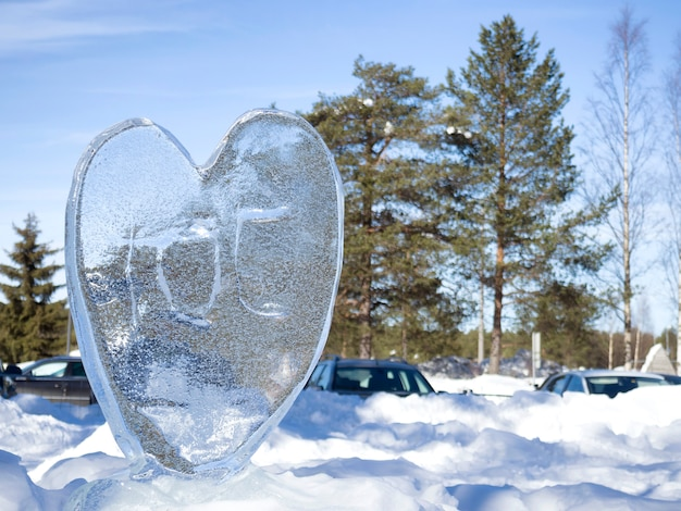 Eis herz im glitzernden schnee mit geringer schärfentiefe.