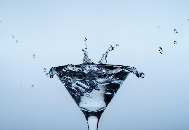 Eis im glas mit wasserspritzer auf blauer oberfläche