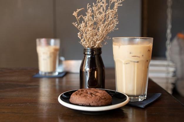 Eis latte coffeein ein glas mit chocolate chip cookie auf einem holztisch