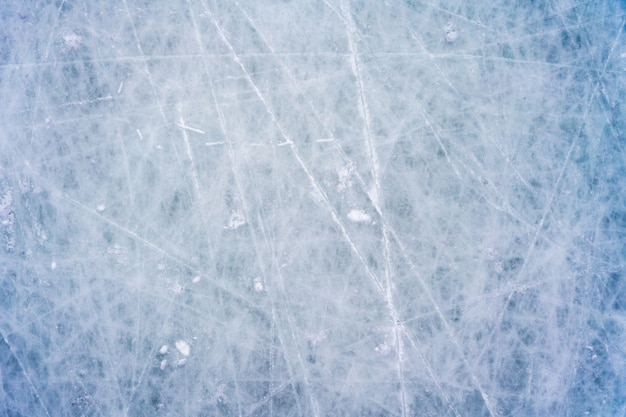 Eis mit flecken von skaten und hockey, blaue textur der eisbahnoberfläche mit kratzern