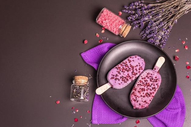 Eis mit lavendelgeschmack. blumenstrauß, rosa zucker, rosenblätter. betonhintergrund aus schwarzem stein, ansicht von oben