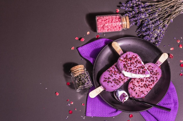 Eis mit lavendelgeschmack. blumenstrauß, rosa zucker, rosenblätter. trendiges hartes licht, dunkler schatten. betonhintergrund aus schwarzem stein, ansicht von oben