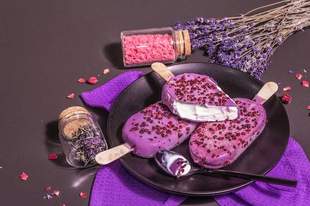 Eis mit lavendelgeschmack. blumenstrauß, rosa zucker, rosenblätter. trendiges hartes licht, dunkler schatten. schwarzer steinbetonhintergrund, kopienraum