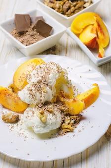 Eis mit pfirsich, schokolade und nüssen.