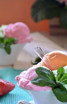 Eis mit verschiedenen geschmacksrichtungen, begleitet von minze, mandarine und erdbeeren