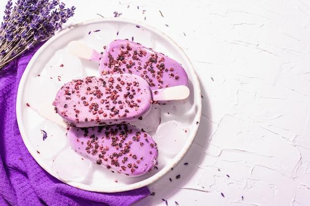 Eis mit violettem lavendelgeschmack. blumenstrauß, vintage silberlöffel, keramikständer. modernes hartes licht, dunkler schatten. weißer kitthintergrund, draufsicht
