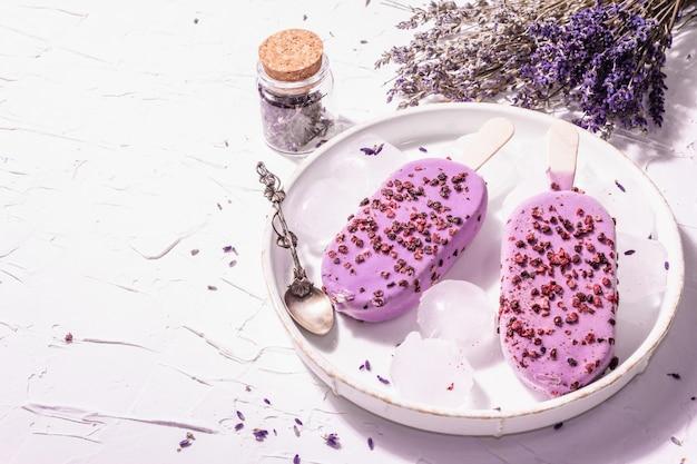 Eis mit violettem lavendelgeschmack. blumenstrauß, vintage silberlöffel, keramikständer. modernes hartes licht, dunkler schatten. weißer kitthintergrund, kopienraum