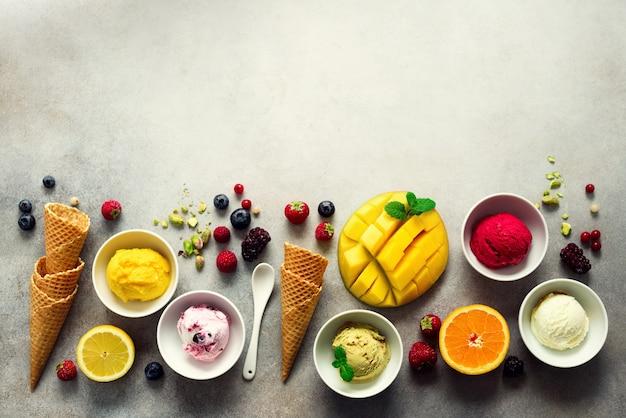 Eisbällchen in schüsseln, waffelhörnern, beeren, orange, mango, pistazien auf grauem beton. bunte sammlung, flache lage, sommerkonzept, draufsicht