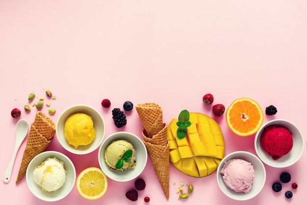 Eisbällchen in schüsseln, waffelhörnern, beeren, orange, mango, pistazien auf rosa shabby chic. bunte sammlung, flache lage, sommerkonzept, draufsicht