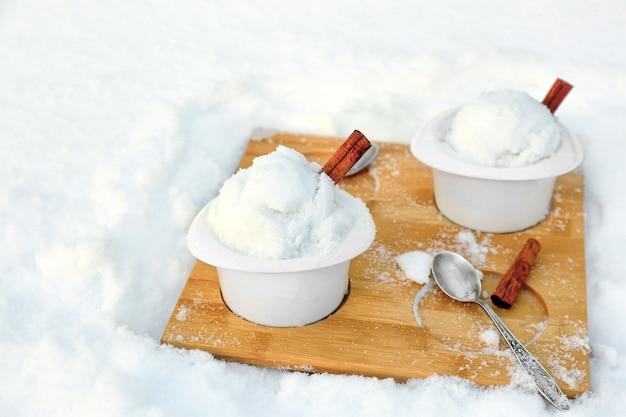 Eisbecher mit schnee auf holzbrett im freien