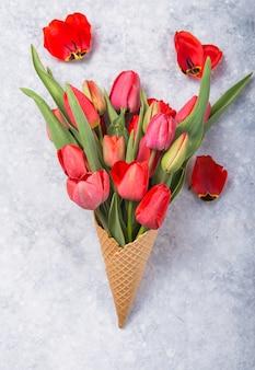 Eiscreme der roten tulpenblumen im waffelkegel auf der draufsicht des betontischs im flachen laienstil.