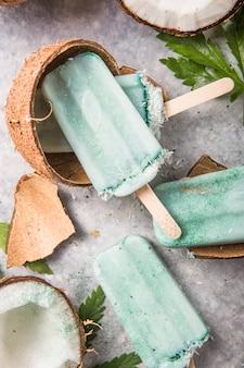 Eiscreme-eis am stiel mit kokosnussscheiben, cannabis auf betonhintergrund.